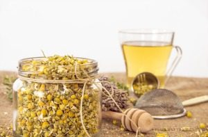 A Jar with Chamomile and Chamomile Tea on Background. Tea arrangement